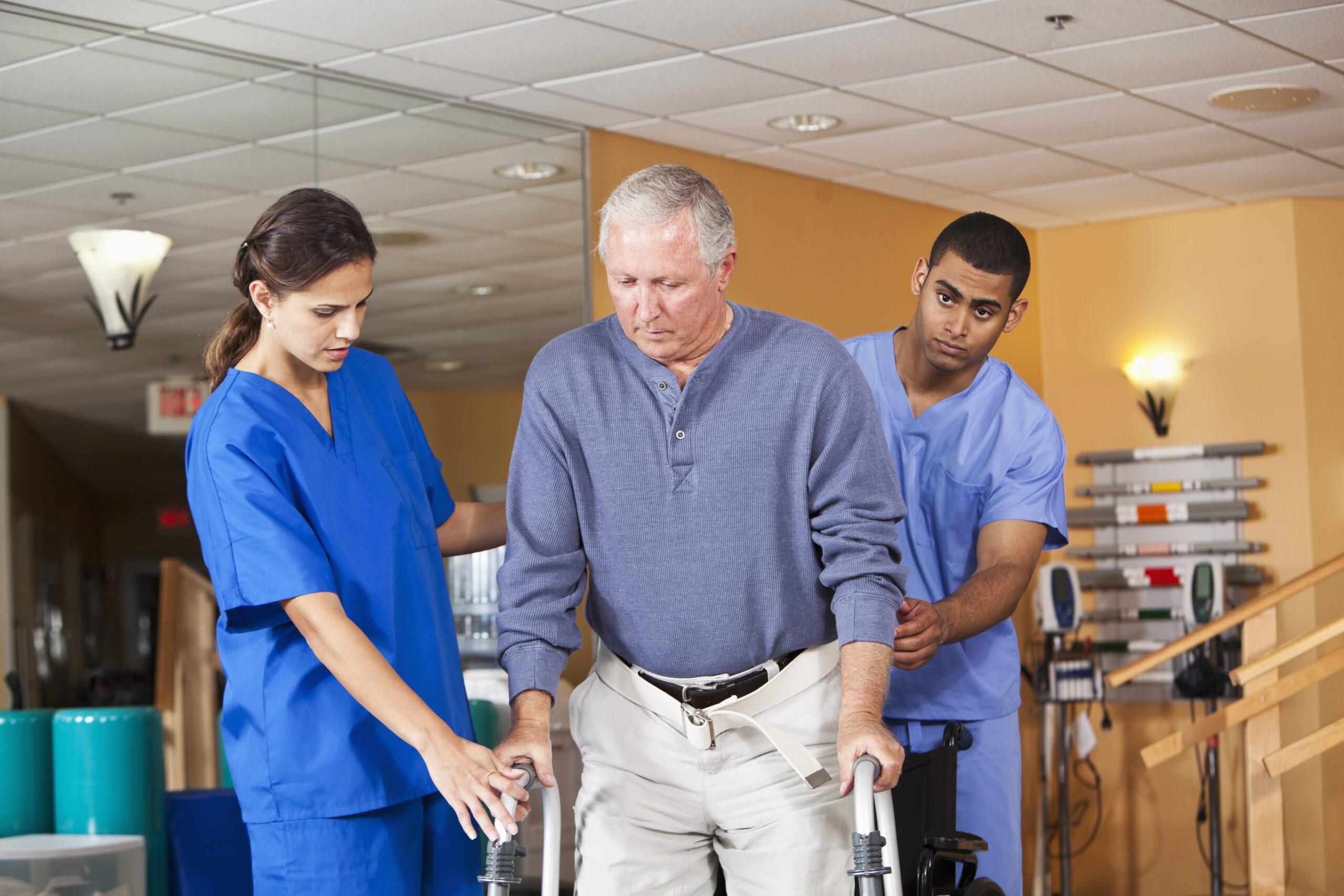 Healthcare workers helping senior man use walker